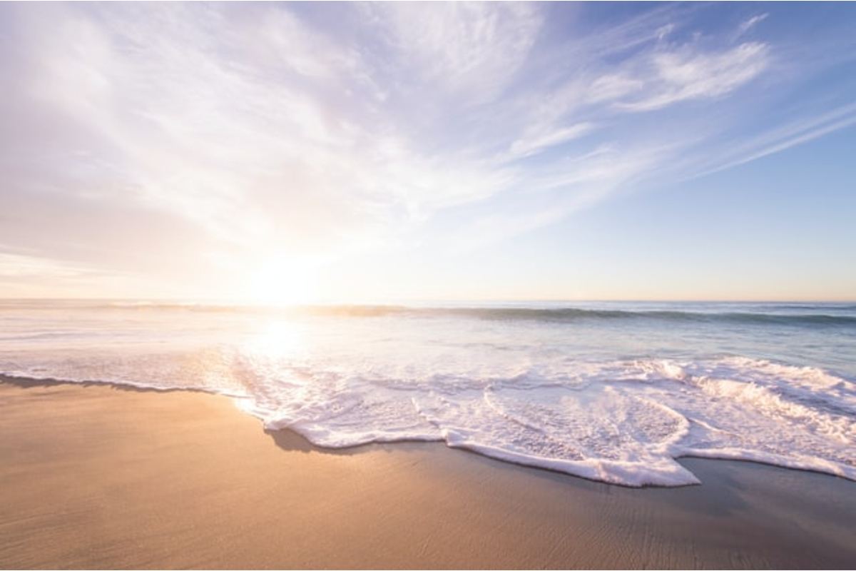 In this image, the sand on the beach is a bright gold, the waves are rushing over the top of the sand and the sun is seating on the horizon, like it is sitting on the water.