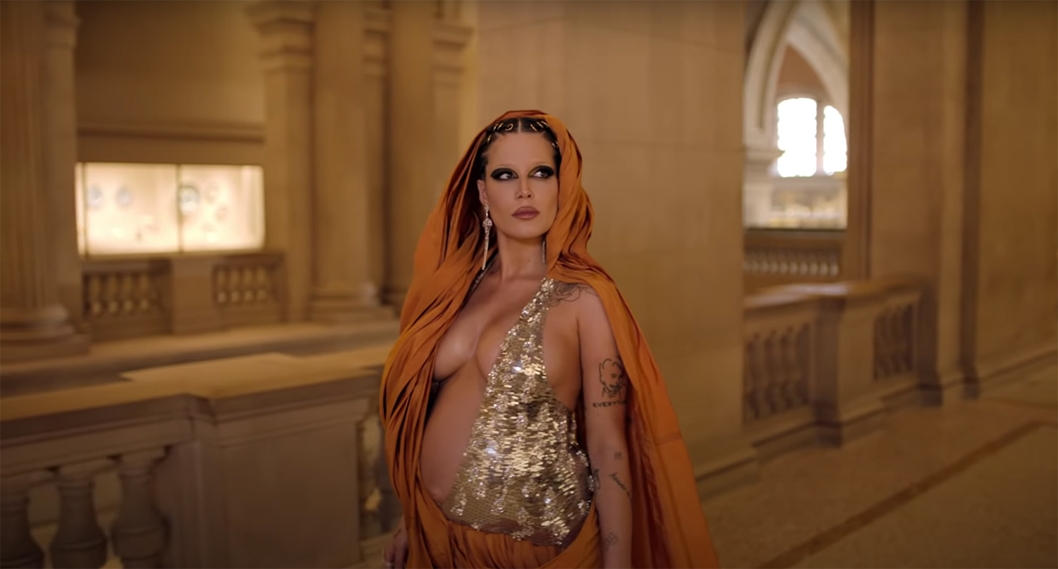 In this image, a heavily pregnant Halsey, poses for the artwork for her upcoming album. Fantasy, revealing costume in a candlelit museum