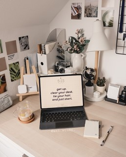 In this image, a laptop is facing the camera and has a quote on it. A small notepad and pen rest to the right of the laptop.