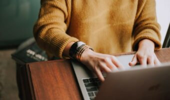 In this image, someone wearing a yellow jumper is typing on a laptop.