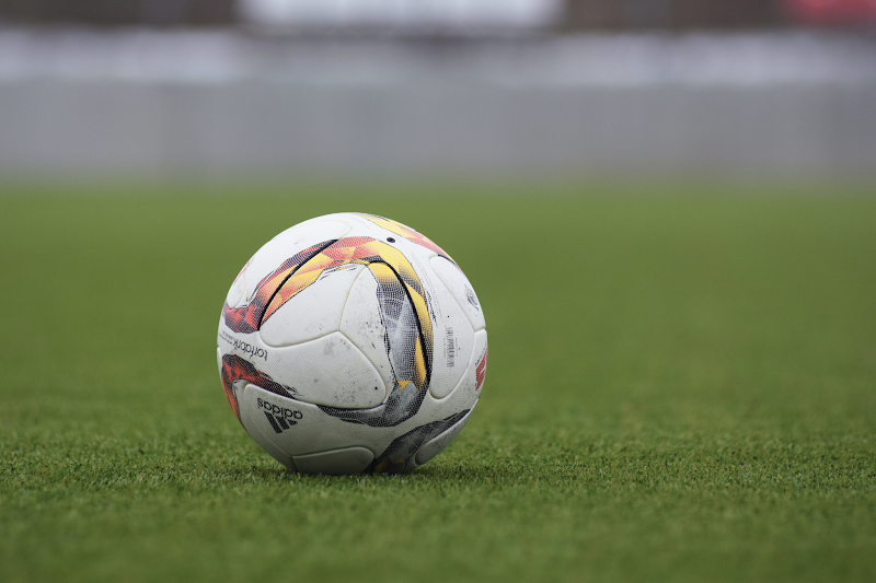 In this image, a white football is sat still on some grass.