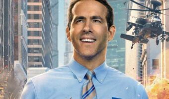 In this image, actor, Ryan Reynolds, is wearing a blue shirt with a name badge on. Behind him is a helicopter, skyscrapers and fire.