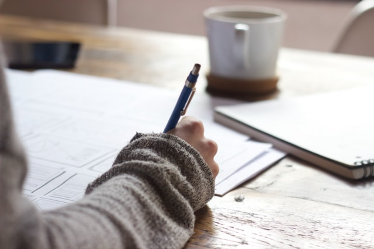 In this image, someone is writing on multiple pieces of paper with a white mug also on the table.