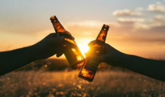 In this image. two people are cheers two beer bottles together. They are sat in a field and the sun is setting between the two bottles.