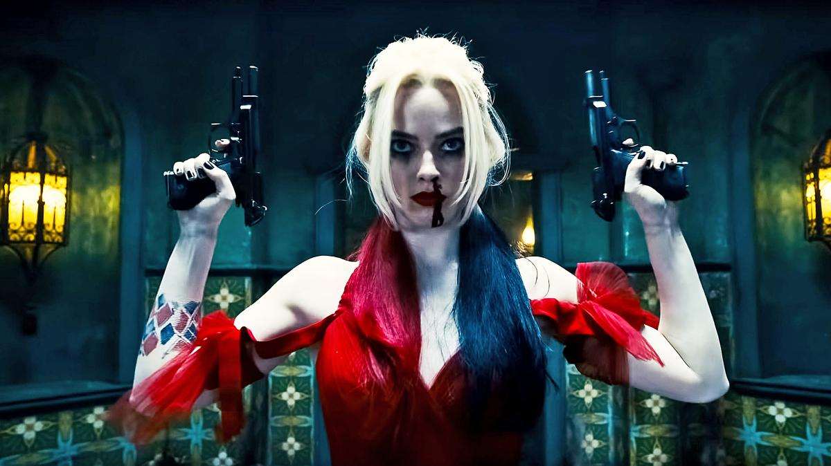 In this image, Harley Quinn (played by Margot Robbie) is wearing a red dress, has blood dripping from her nose down her face and his holding two black pistols in her hands. Both pistols are pointing up to the sky.