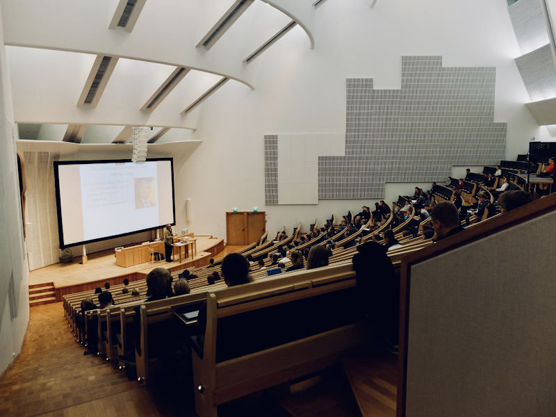 In this image, a lecturer is teaching at the bottom of a lecture hall. Some students are sat at their desks.