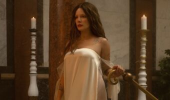In this image,A woman in her mid twenties is in a white, silk, strapless dress. She faces away from the camera, looking forward as she walks through a hallway that mimics an art gallery.