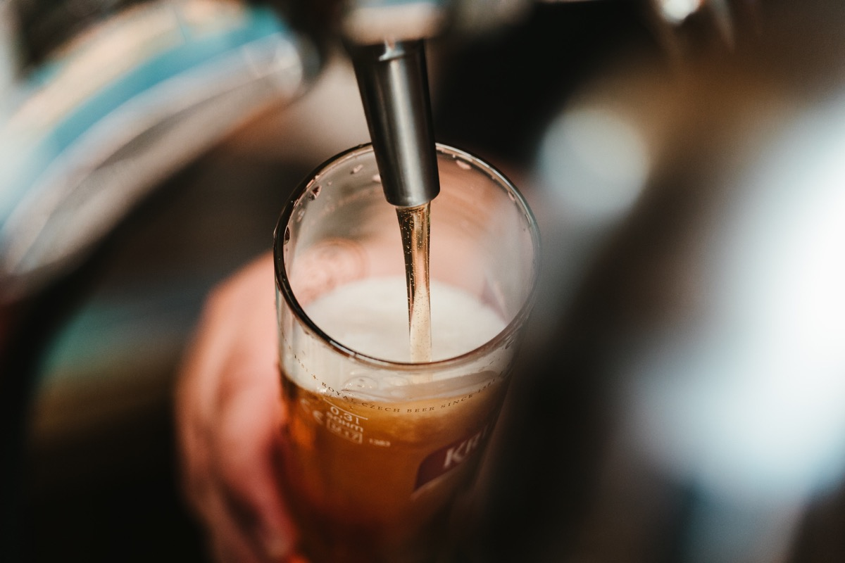 This image shows someone pulling a pint into a clear glass.