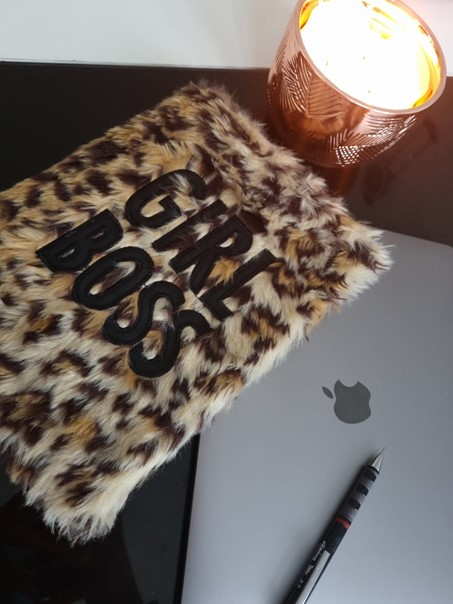 """In this image, there is a lit candle, a furry notebook that has """"GIRL BOSS"""" written on the front. Underneath the notebook is a laptop with a black pen on top of it."""