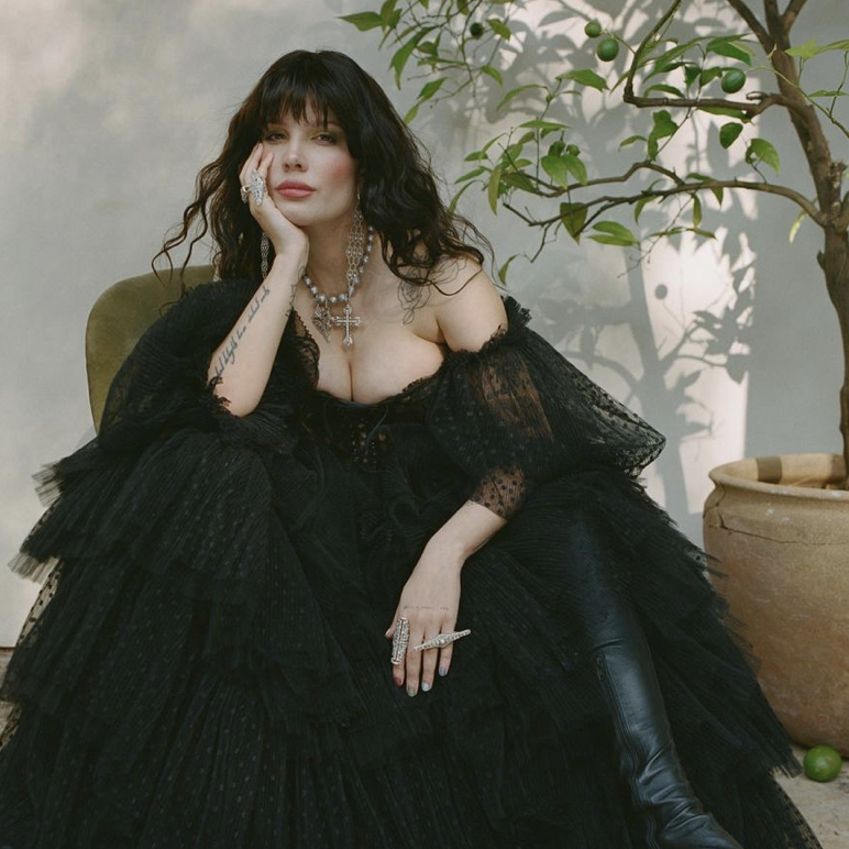 In this image, Halsey poses in black, gothic ballgown in front of white wall with her chin in her hand
