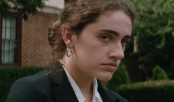 This is an image of actress, Rachel Sennott, in Shiva Baby. She has her brown hair tied up and is wearing a white shirt and black blazer.