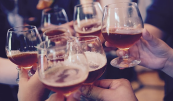 In this image, a group of people are clinking their drinking glasses together.