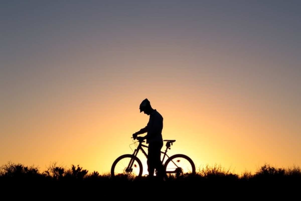 In this image, a silhouette of a man with a bike. The sun is setting behind him.