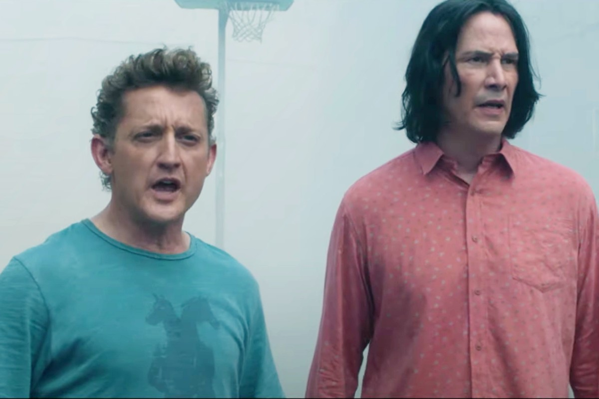 In this image, two men are stood and looking at something off-camera, to the right. The man on the left is smaller, has grey hair and is wearing a blue top. The guy on the right is taller, has long dark hair and is wearing a red shirt.
