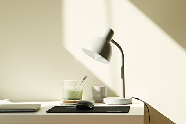 This is an image of a white desk lamp at the corner of a desk. On the desk is a glass of milk, a computer mouse and a black mousepad.