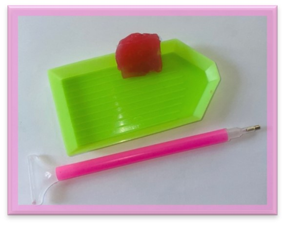 In this image, there is a green tray, a pink tool.