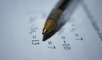 A pen lies on top of a maths equation.