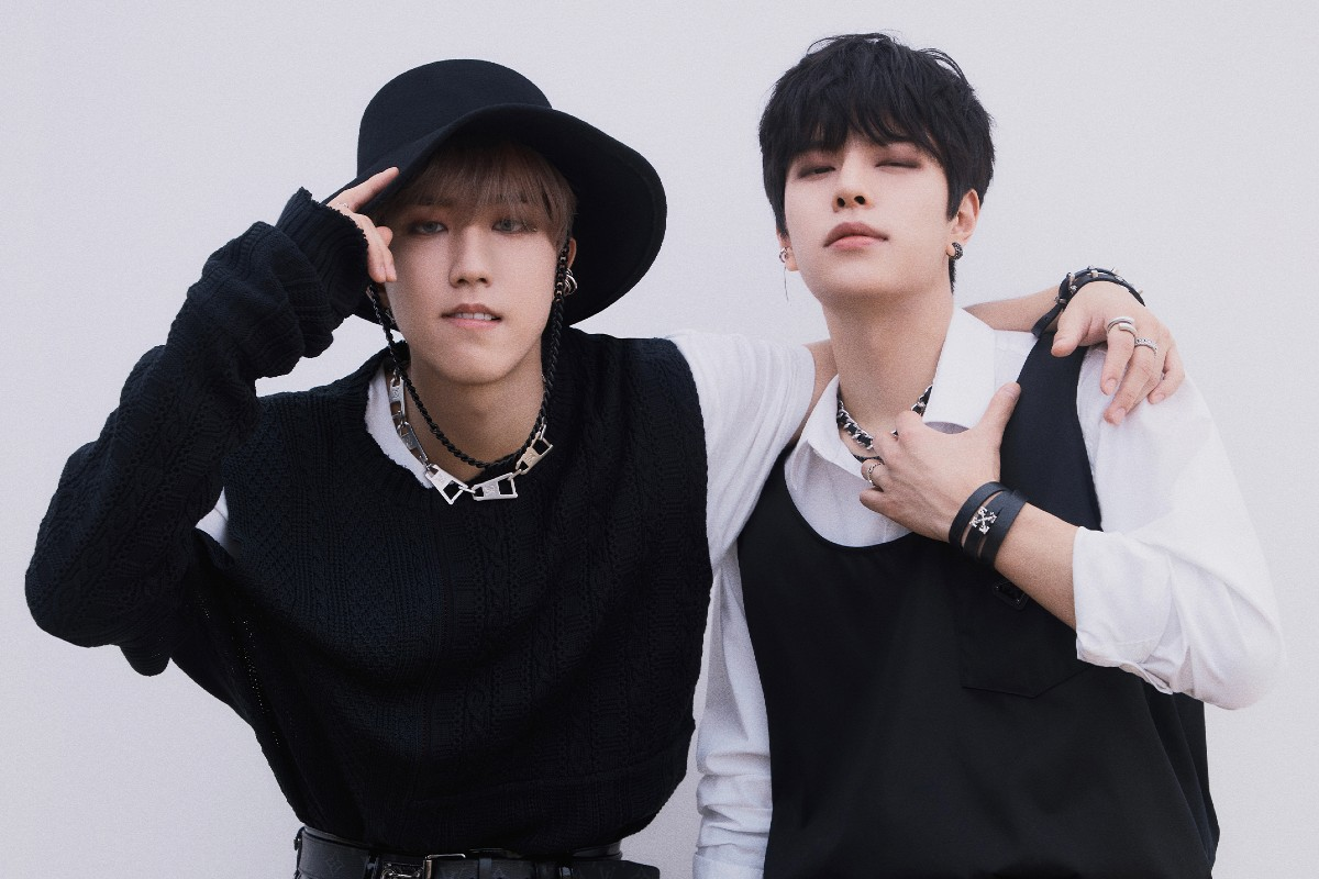 In this image, Han and Seungmin have their arms over each other and facing the camera. They are both wearing outfits made of black and white clothing.