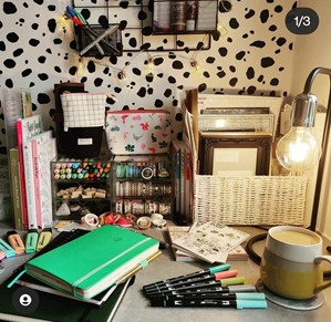 This is an image of Jess' desk layout. There are textbooks stacked on the desk, things hung on the wall. At the back of the desk are organisers with things in them. Her wall has a Dalmatian pattern on it.