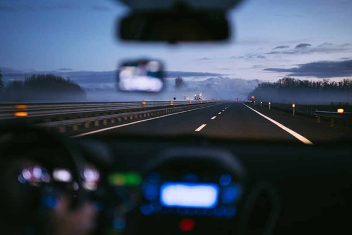 The images is blurred as an effect. It is someone driving on an empty road as it's getting dark.