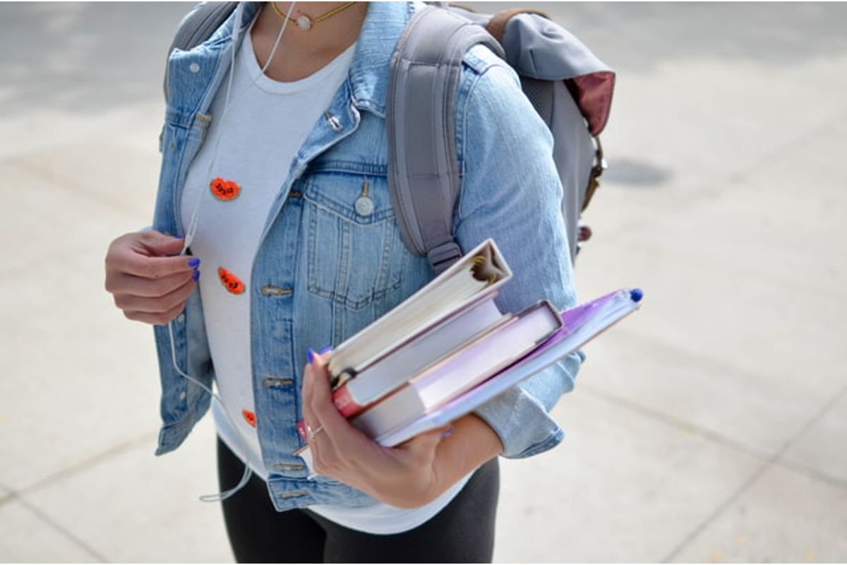In this image, a woman is holding some books in her arm. She is wearing a backpack and presumably attending an educational establishment.
