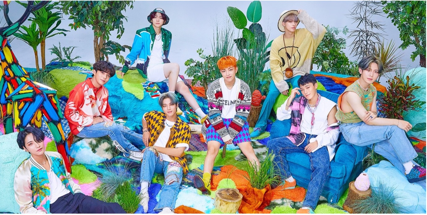 In this image is K-pop boyband ATEEZ posing for their album in this colourful photoshoot. The 8 members are seated in various places in front of a woodland background.