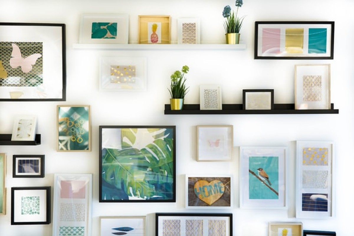 This images show lots of photo frames hanging on a wall. They are different colours of wood and different shapes.