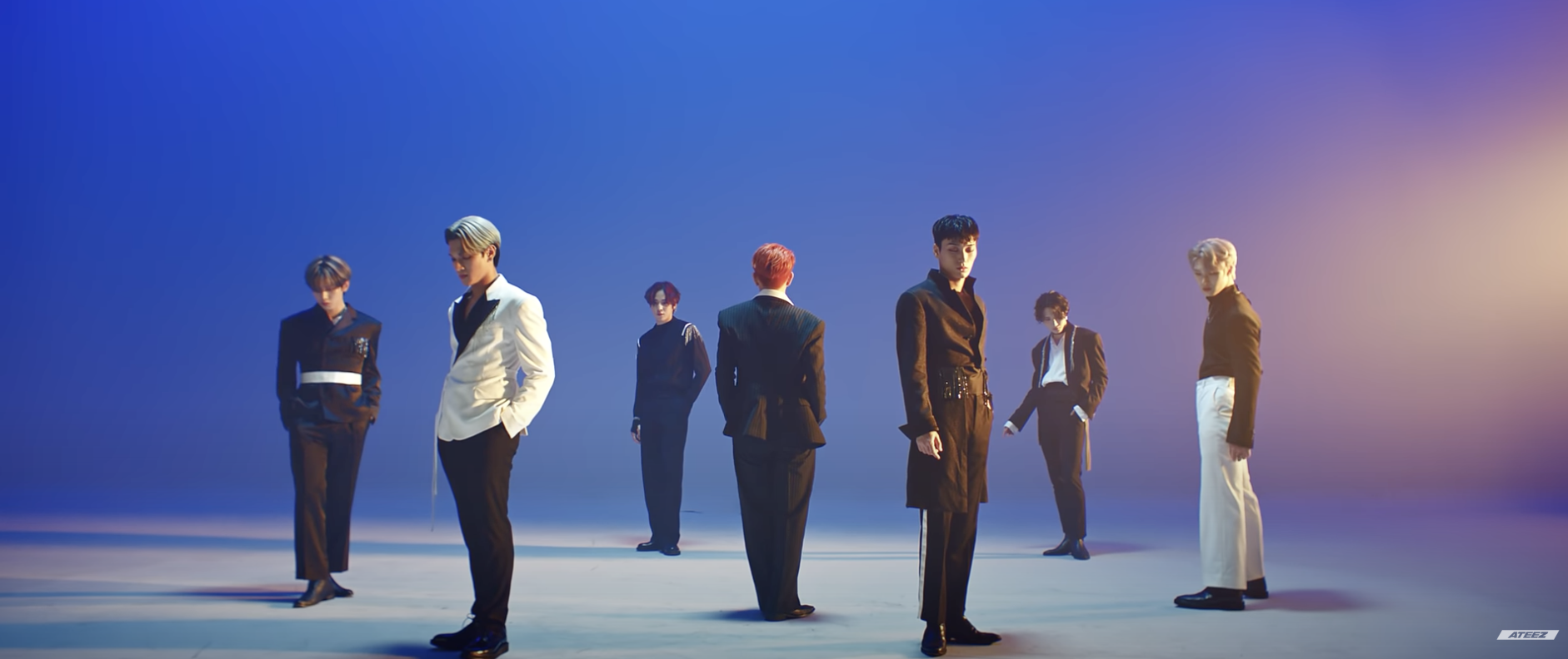 """This image is a screenshot of K-Pop boyband, ATEEZ, from their performance video for their song """"Deja Vu"""". In front of a blue tinted background, they are standing at different points of the room all dressed in formal attire."""