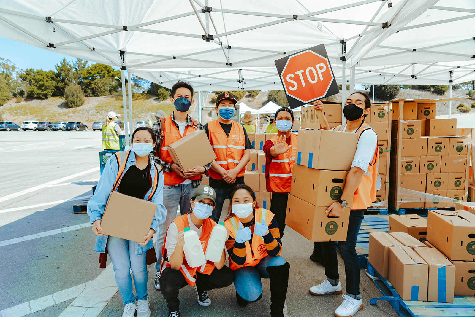 In this image, the Belugabee team are wearing medical masks and orange jackets. They are holding stop signs and cardboard boxes.