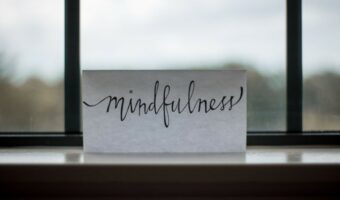"""In this image, a piece of rectangular paper is resting against a window and has """"mindfulness"""" written on it."""