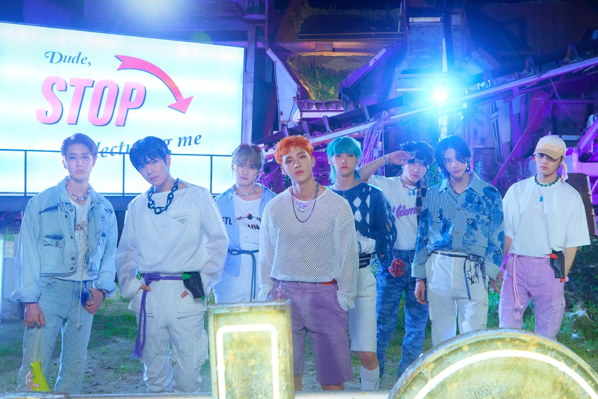 In this image, Stray Kids are lined up horizontally and stood facing the camera. They are all wearing outfits that are colour codes white, purple and blue.