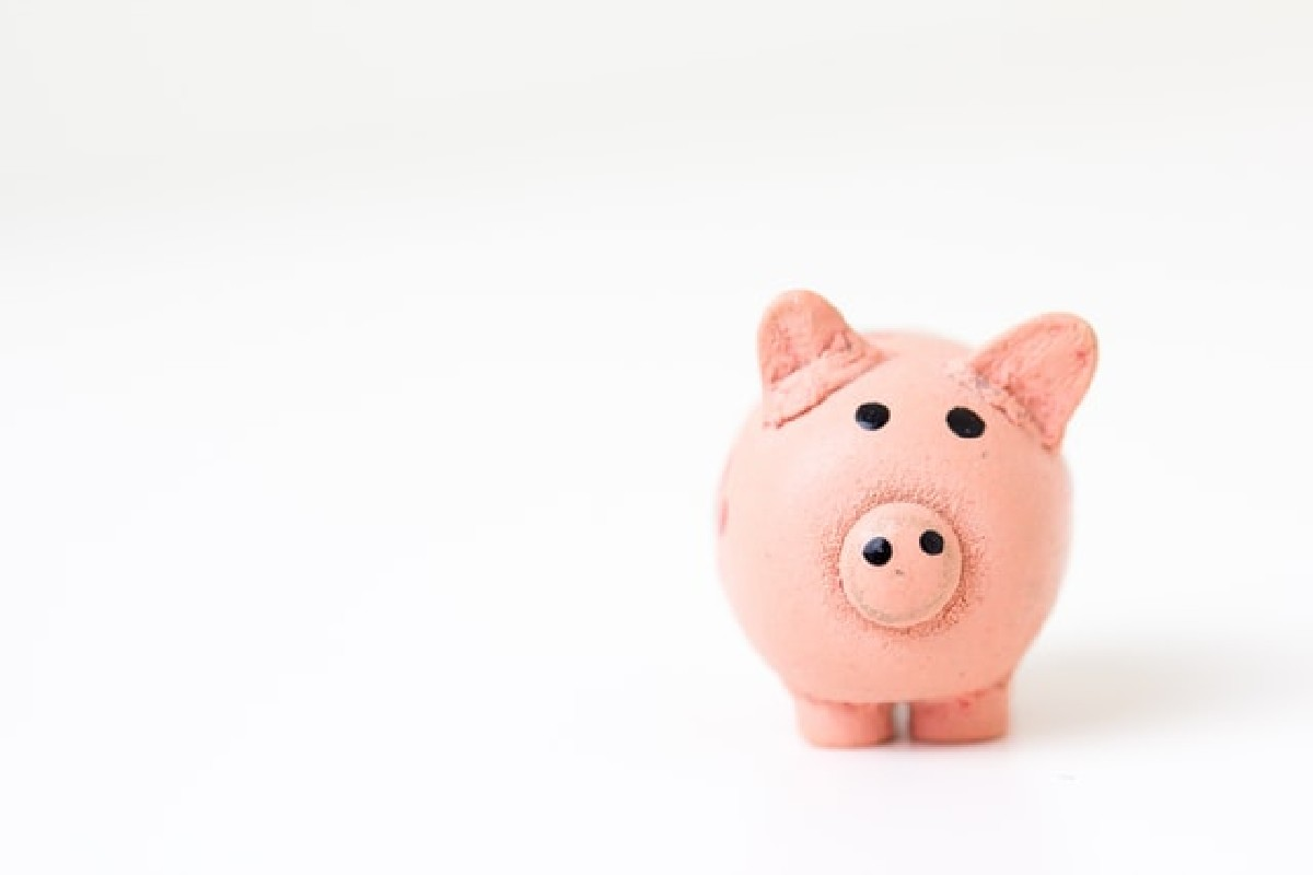 In this image, a pink piggy bank has been placed to the right side of the image. Everything surrounding it is white.