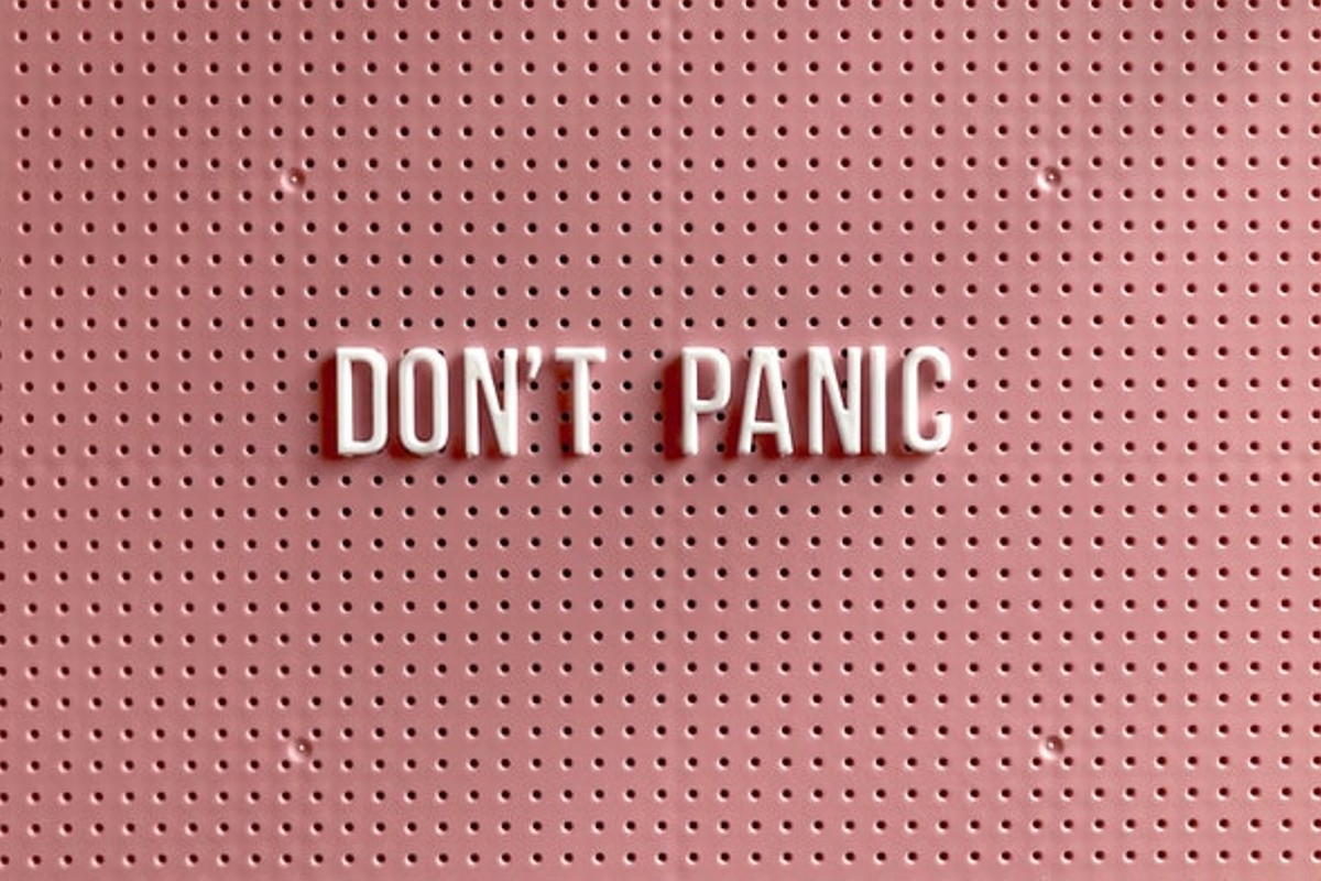 """The image is all in pink. It says """"Don't Panic"""" in the middle, also in pink."""