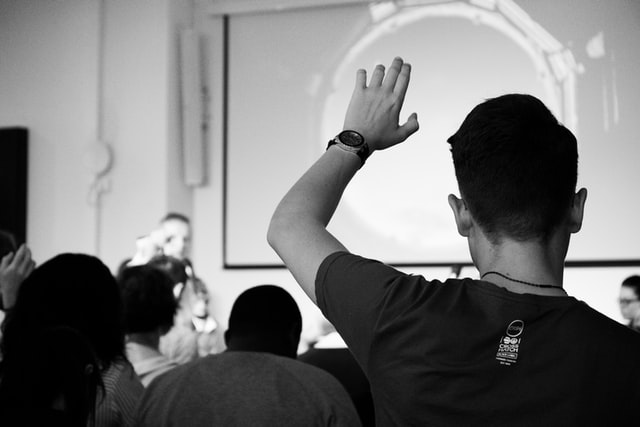 This image has a black and white effect to it. A man is raising his hand in the air, perhaps wanting to ask a question to the person stood at the front of the room.