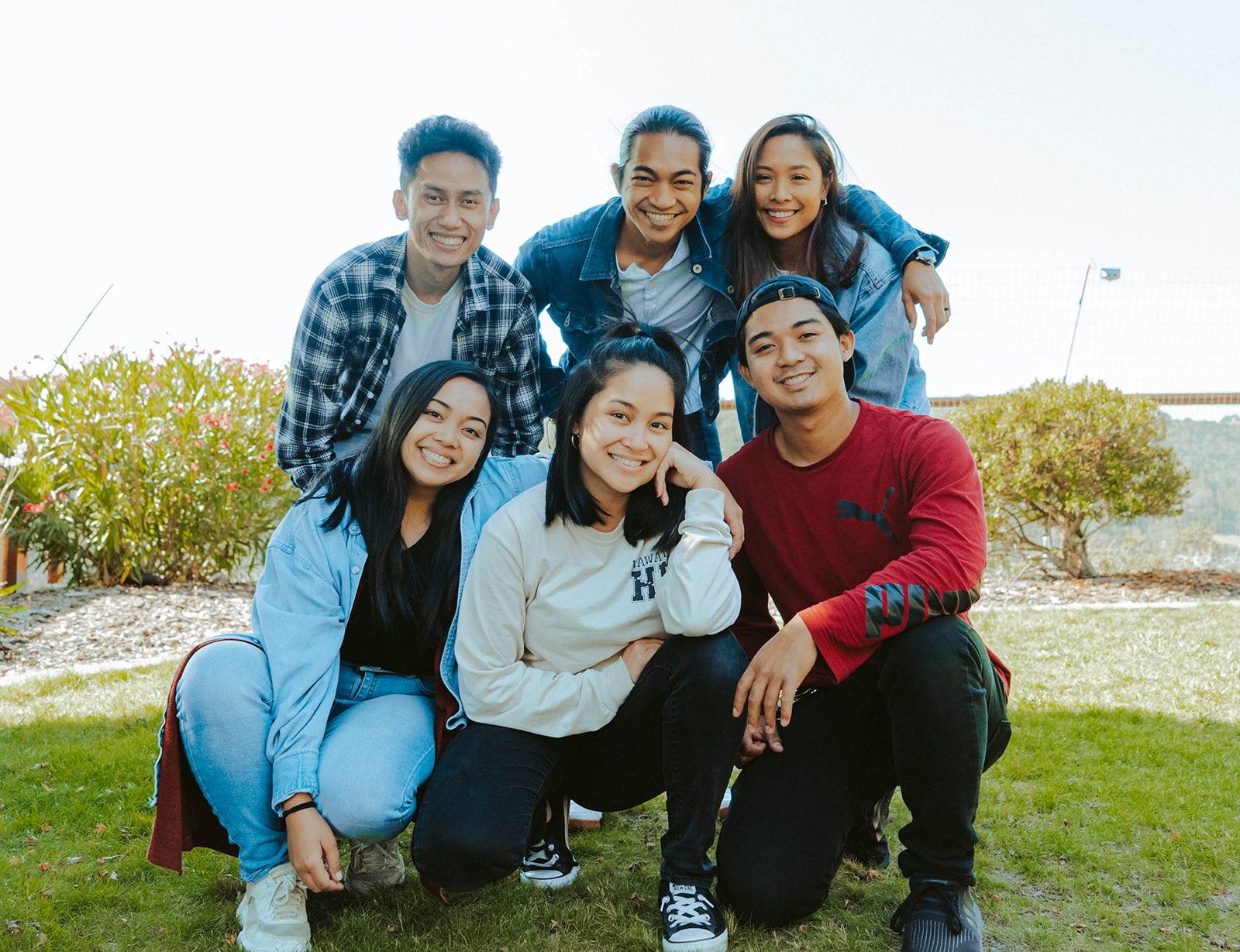 This is an image of the whole Belugabee team. Two girls and one boy are knelt at the front and two boys and one girl are stood at the back. They are all dressed in casual clothing and have taken the photo in a field.