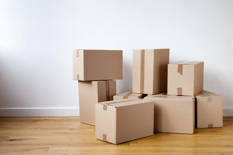 In this image are piled up cardboard boxes in an empty bedroom.