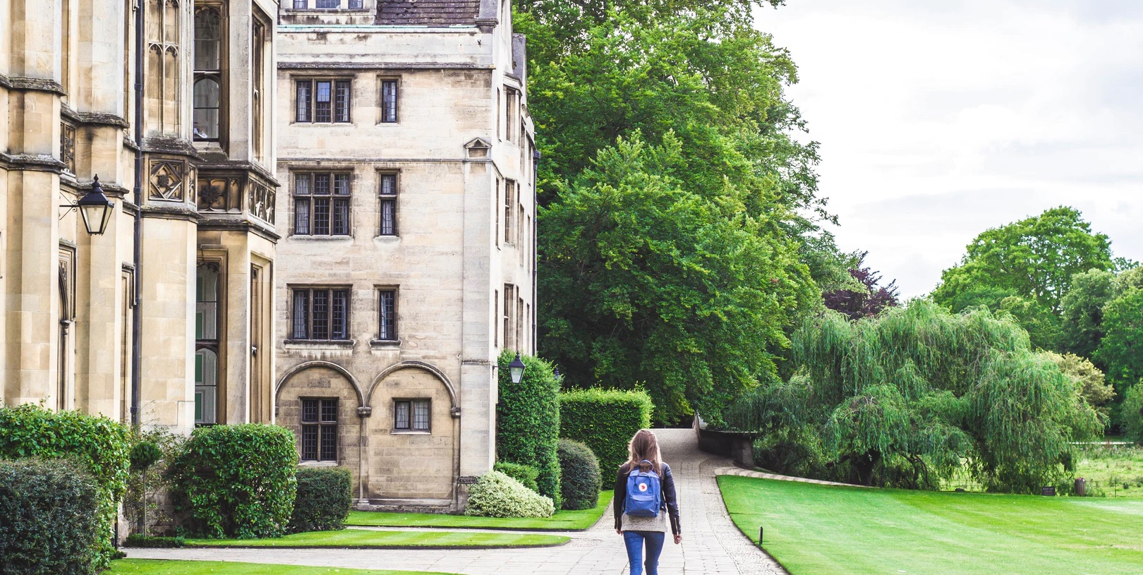 In this image, is a long shot of a girl entering her university hall.