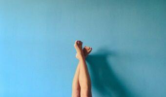 Against a blue backfround, someone has their feet in the air.