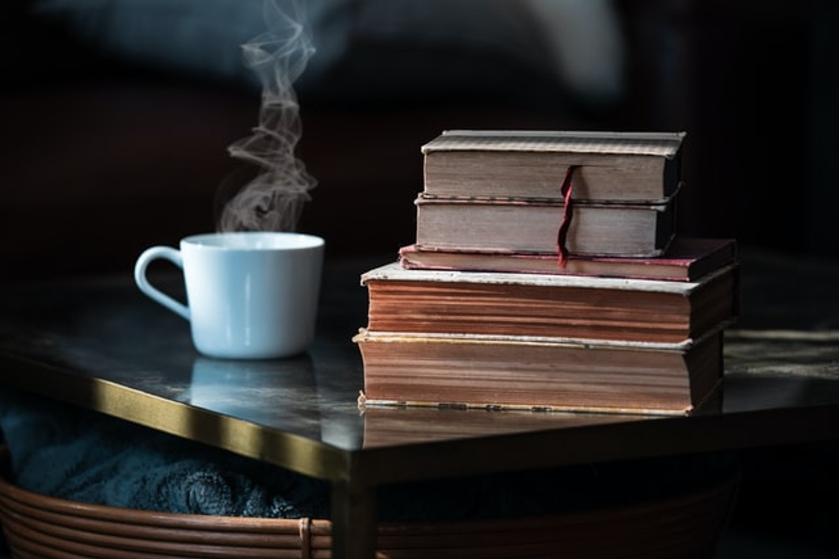 In this image is a pile of books, the smallest being at the top and the biggest being at the bottom. Next to this pile is a mug and it has a hot drink inside as steam is rising from the mouth of the mug.