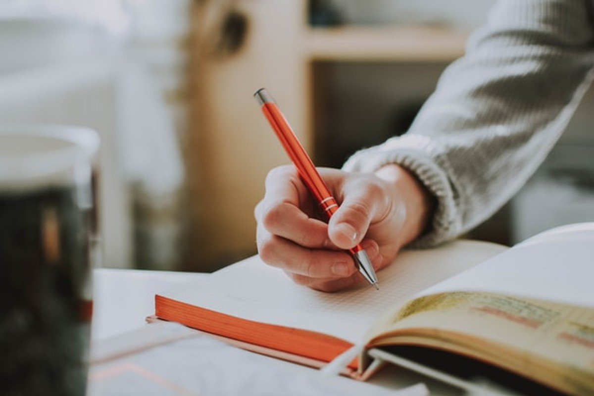 In this image, someone is using an orange pen to write in a journal.